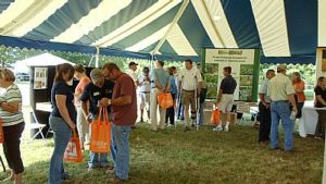 Field Day visitors enjoying exhibits under large tent